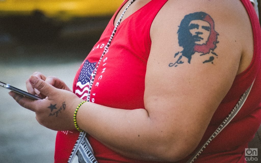 Detail of a Cuban woman at a Havana bus stop: Che Guevara is tattooed on her shoulder. On her wrist is an Orula bracelet, for the orisha of divination, the supreme oracle and the great benefactor of humanity and her chief advisor. She is wearing a t-shirt with the flag of the United States. Photo: Kaloian Santos