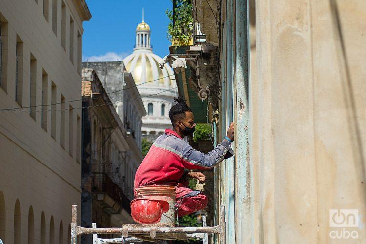 Constructor repara la fachada de un edificio en la calle Obrapía, La Habana. Foto: Otmaro Rodríguez