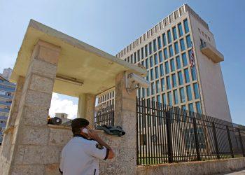 Un guarda de seguridad habla por teléfono frente al edificio de la embajada de EEUU en La Habana. | Reuters