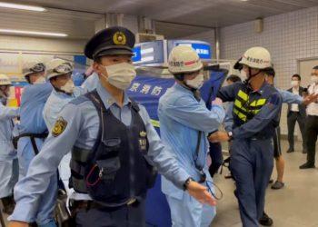La policía escolta a rescatistas que llevan a una persona herida después de un ataque con cuchillo en un tren en Tokio. Foto: Al Jazeera.