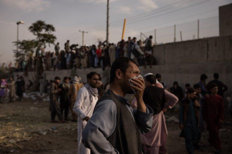Un hombre se seca las lágrimas frente al muro del aeropuerto de Kabul, donde la evacuación es lenta y dìficil.   Foto: NYT