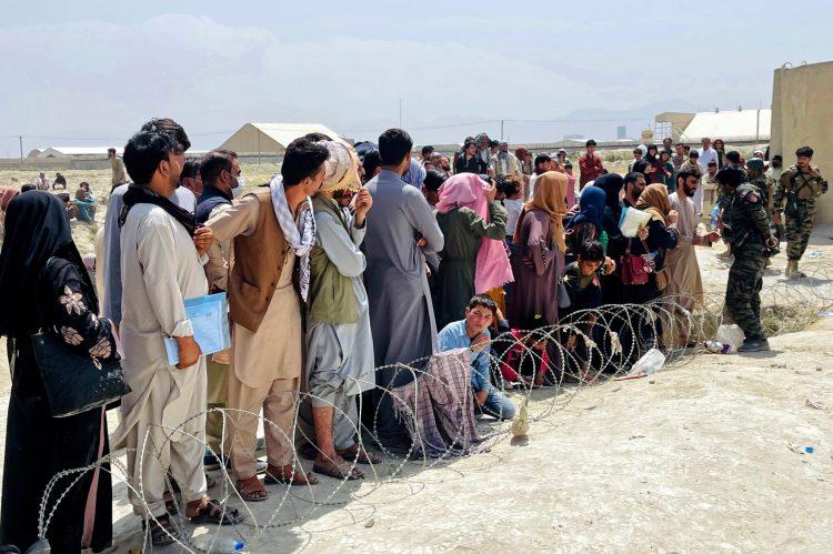 Guardias de seguridad afganos tratan de mantener el orden mientras cientos de personas se congregaban en las afueras del aeropuerto internacional en Kabul, Afganistán, este martes, para poder escapar del país. Foto: The Associated Press.