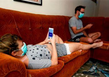 Una pareja revisa sus teléfonos celulares dentro de su casa durante la cuarentena por la pandemia de COVID-19 en La Habana. Foto: Ernesto Mastrascusa / EFE / Archivo.
