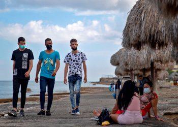 Un grupo de jóvenes en el paseo marítimo del municipio Playa, tras el inicio de la desescalada en La Habana. Foto: Yander Zamora / EFE.