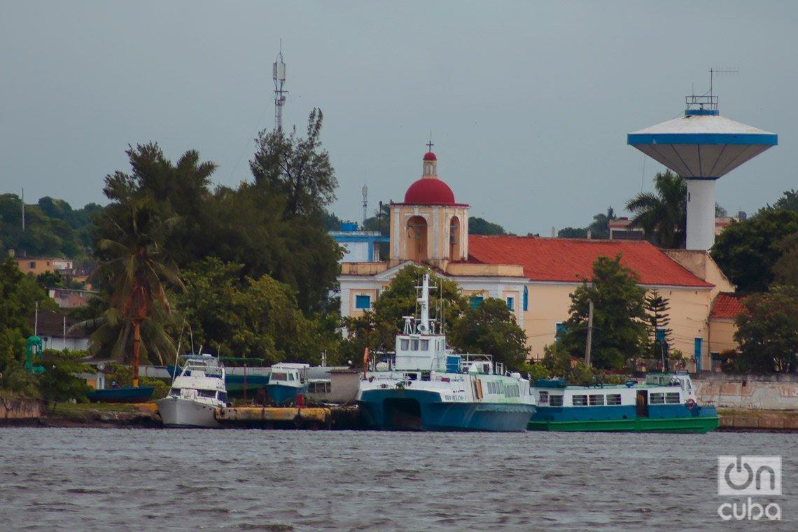 Santuario de La Virgen de Regla, en el poblado homónimo, en La Habana. Delante, varias embarcaciones atracadas, entre ellas una de las lanchitas que unen esa localidad ultramarina con el centro histórico habanero. Foto: Otmaro Rodríguez.