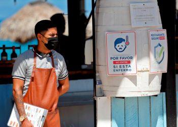 Un trabajador de un restaurante, en La Habana, tras la reapertura de sus servicios en mesa como parte de la nueva desescalada en Cuba. Foto: Ernesto Mastrascusa / EFE.