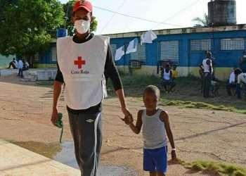 Un voluntario cubano de la Cruz Roja junto a un niño haitiano en un campamento de migrantes en el norte de Camagüey, Cuba. Foto: Rodolfo Blanco / ACN.