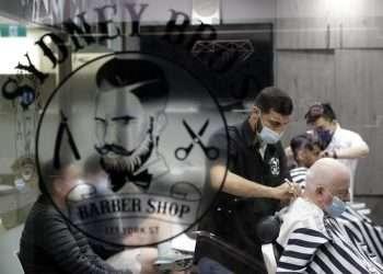 Una barbero atiende a sus primeros clientes hoy lunes 11 de octubre al cabo de más de cien días de cierre en Sydney, Autralia. Foto: Rick Rycroft/AP.