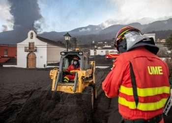 Personal de la Unidad de Emergencia Militar limpia ceniza negra del volcán mientras continúa haciendo erupción de lava detrás de una iglesia en la isla de La Palma. Foto: Saul Santos/AP.