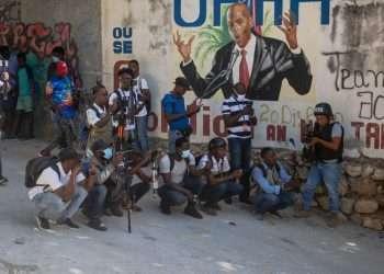 Varios haitianos, junto a un mural del presidente asesinado, Juvenal Moïse, en Puerto Príncipe. | Foto: EFE