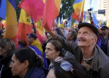 Manifestantes con banderas durante una protesta contra el gobierno organizada por la Alianza para la Unidad de los Rumanos (AUR) en Bucarest, Rumania, el sábado 2 de octubre de 2021. Foto: Vadim Ghirda/AP.