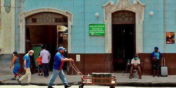 Un hombre mientras camina con una carretilla frente a un policlínico en La Habana, provincia con una de las tasas de incidencias más bajas al cierre de mes. Foto: Ernesto Mastrascusa/Efe.